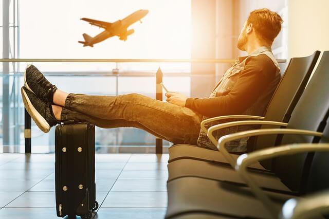Ritardo aereo: un ragazzo che aspetta in aeroporto il suo volo mentre guarda fuori e vede un aereo decollare.