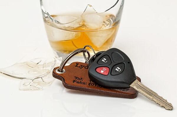 Guida in stato di ebbrezza: la foto mostra un bicchiere rotto ma ancora pieno di alcol e delle chiavi di un'auto.