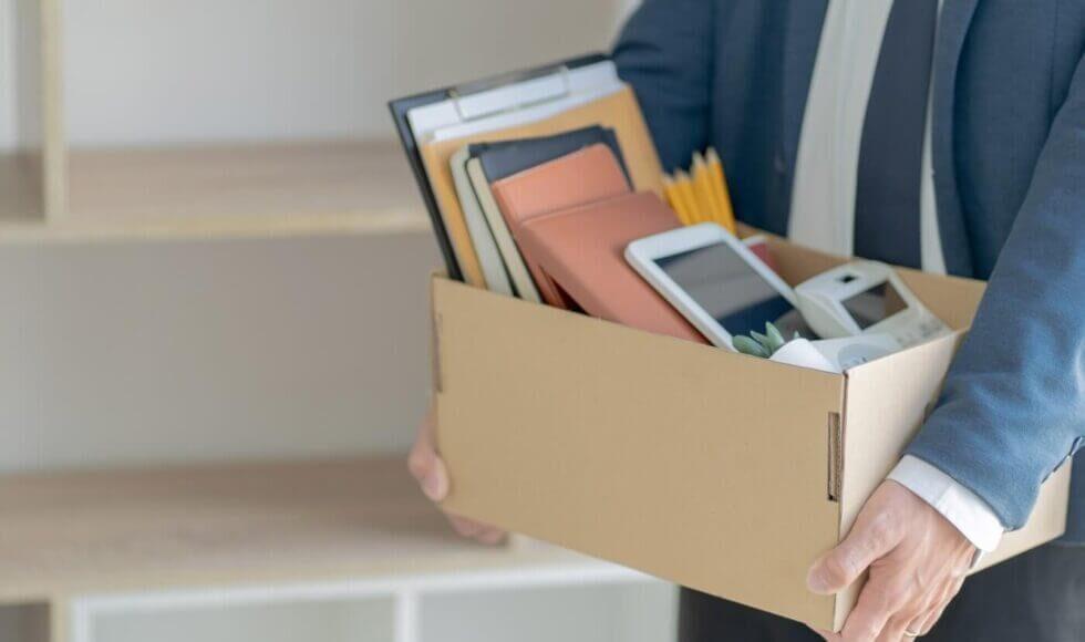 Lettera di dimissioni: nella foto si vede una persona che mantiene in mano una scatola piena di oggetti utili al lavoro di ufficio.