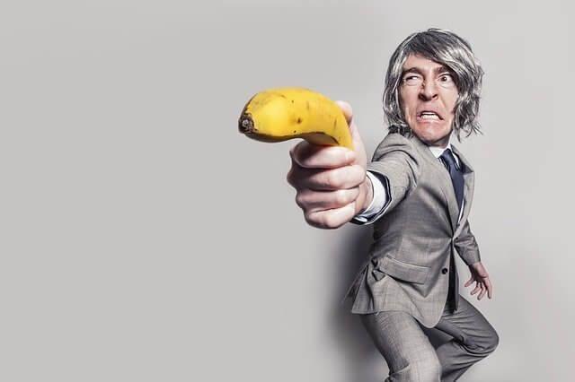 Il datore di lavoro può ascoltare le telefonate dei dipendenti? Questa immagine mostra un uomo in giacca e cravatta che minaccia qualcuno con una banana in mano.